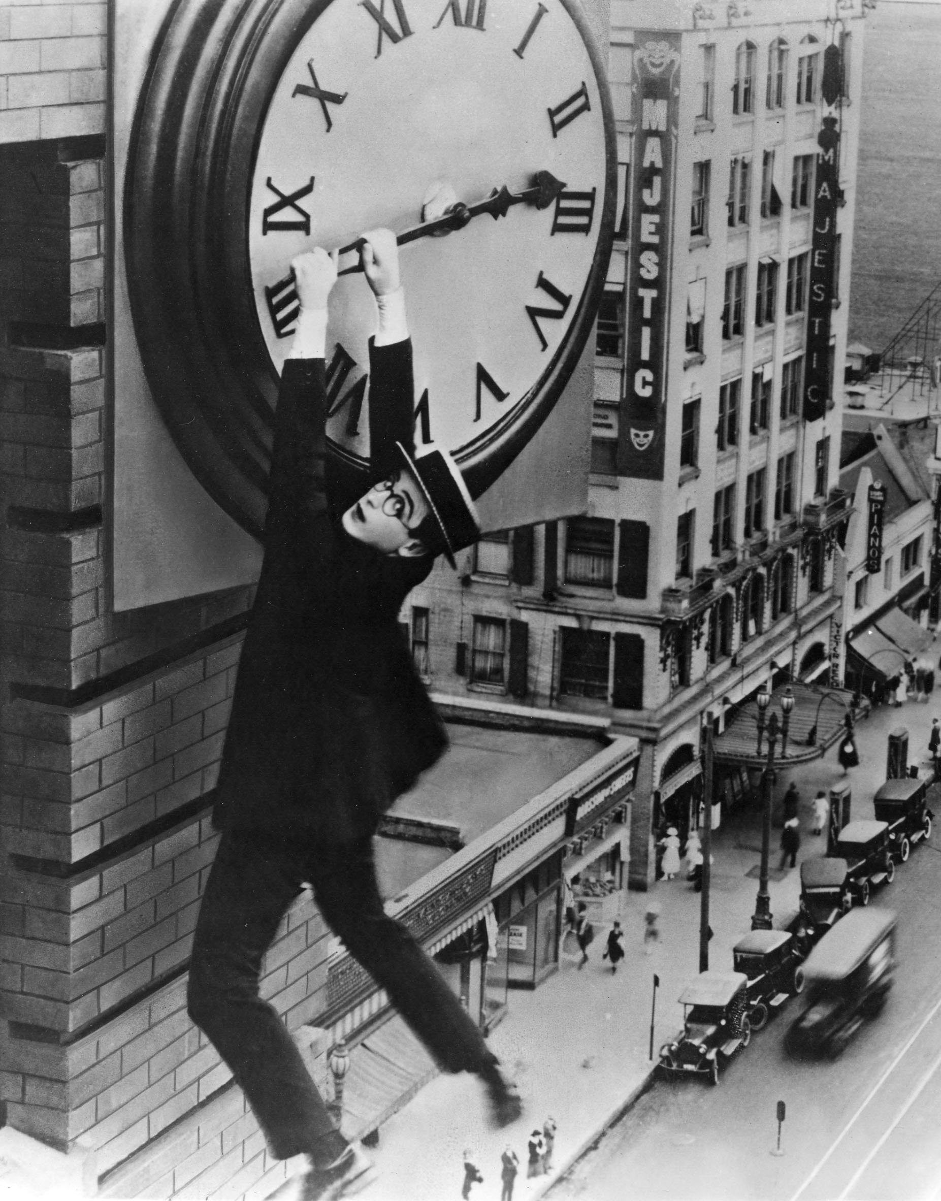 Haold Lloyd dangles from a clock high above a street stopping time itself even as daylight savings time fights crime by making criminals less likely to act.