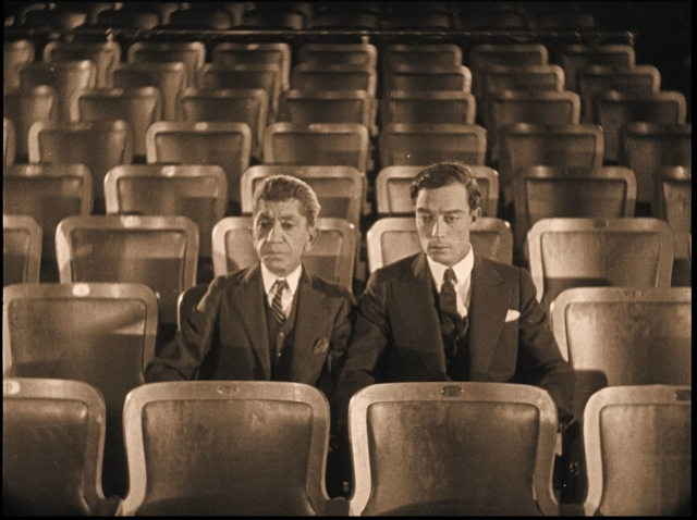 Buster and his valet, played by Snitz Edwards, sit stunned in Olympic Auditorium, after the formerly obscure boxer who shares Keaton's name has unexpectedly become champion.
