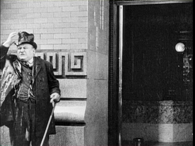 The same entrance to the bank appears during this scene from Charlie Chaplin's The New Janitor (1914).