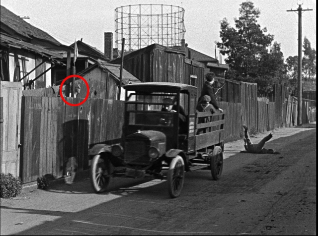 This neighbor suddenly peeks over the fence as the orphanage truck travels west down Labory Lane.