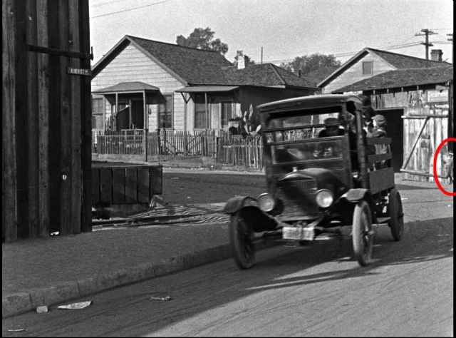This real-like waif watches Jackie Coogan in the orphanage truck as it turns from the east end of Labory Lane onto Hewitt.