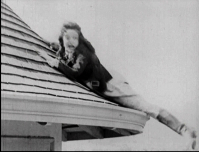 Mable Normand clings to the roof of the Castle Towers Apartment in Mickey.